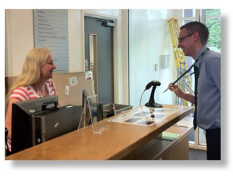 Visitor checking in at school reception with scanner | Visitor Management Software Solutions | SG World