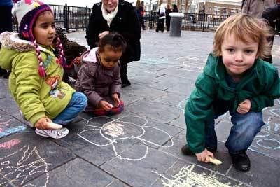 Children playing with Chalk on a pavement - SG World